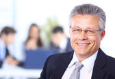 Smiling businessman in his office — Stock Photo