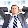 Relaxed and dreaming business man sits on office chair - Stock Photo