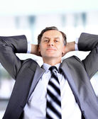Relaxed and dreaming business man sits on office chair — Stock Photo