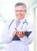 Closeup portrait of a happy young doctor with stethoscope in hospital writi — Stock Photo