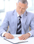 Portrait of smiling Senior business man writing on notepad — Stock Photo