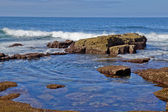Waves breaking againt rocky coast — Stock Photo
