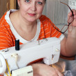 Royalty-Free Stock Photo: Old woman sews clothes in-home