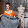 Old woman sews clothes in-home — Photo