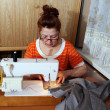Old woman sews clothes in-home — Stock Photo #5550646