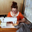 Stock Photo: Old woman sews clothes in-home