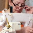 Old woman sews clothes in-home — Stock Photo