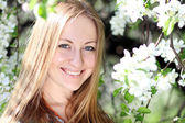 Portrait of beautiful blond in spring blossom — Stock Photo
