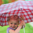 Little girl with a umbrella in park — Stock Photo