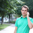 Foto Stock: Young attractive man calling by phone