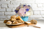 Peony and cornflower bouquet with some bread — Stock Photo