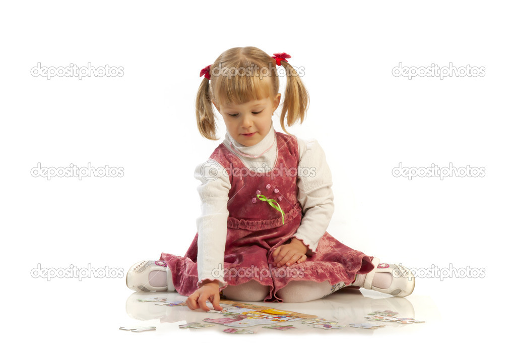 Small girl collecting a puzzle  Stock Photo #6726132