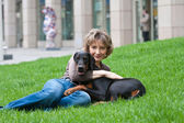 The young woman with a dog on a grass — Stock Photo
