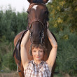 Woman hold horses head up — Stock Photo
