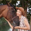 Woman in hat embrace brown horse — Stock Photo