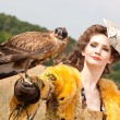 The woman in a beautiful old style dress with falcon has a rest - Stock Photo