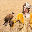 Womin beautiful old style dress with falcon has rest — Stock Photo #6412522