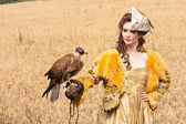 The woman in a beautiful old style dress with falcon has a rest — Stock Photo