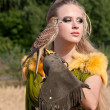 Stock Photo: The woman in a beautiful old style dress with falcon