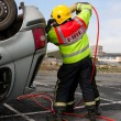 Fireman with Power Wedge at car crash resque - Stock Photo