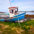 Old Fishing Boat on the bank of Ocean Bay - Stock Photo