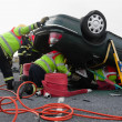 Firemen with equipment at car crash - Stock Photo