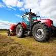 Tractor collecting haystack in the field - Stock Photo
