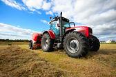 Traktor sammeln heuhaufen im feld — Stockfoto