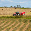 Tractor collecting haystack in the field — Стоковая фотография