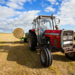 Tractor collecting a roll of haystack in the field - Stockfoto