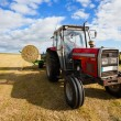 Tractor collecting a roll of haystack in the field - Stock Photo