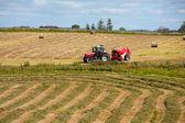 Ciągnik zbieranie stogu siana w polu — Zdjęcie stockowe