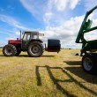 Stock Photo: Tractor collecting a roll of haystack in the field