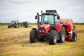 два трактора, собирая стоге сена в поле — Стоковое фото