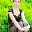 Elegant girl sitting in grass — Stock Photo