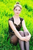 элегантная девушка, сидя в траве — Стоковое фото