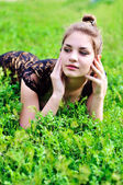 Girl laying in bright green grass — Stock Photo