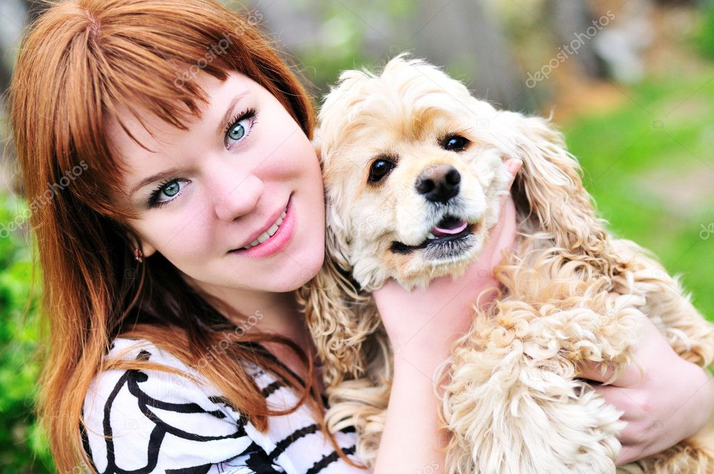 Redheaded pretty girl hugging her dog (american cocker spaniel) on the meadow — Stock Photo #5620273