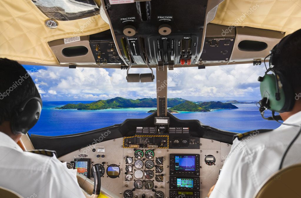Pilots in the plane cockpit and tropical island — Stock Photo #5601768