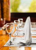 Glasses and plates on table in restaurant — Stock Photo