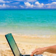 Computer and hand on beach — Stock Photo