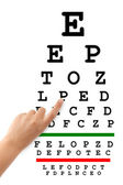 Pointing hand and eyesight test chart — Stock Photo