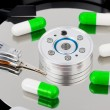 Pills on computer hard drive - Stockfoto