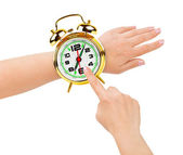 Hands and alarm clock like a watch — Stockfoto