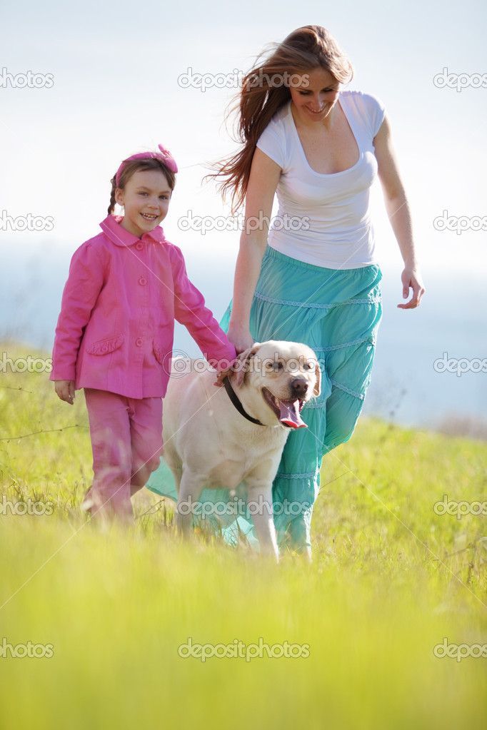 Happy family walking with dog in green field — Stock Photo #5547784