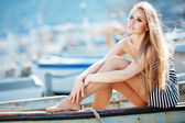Beautiful sexy woman wearing sailor striped dress posing in boat — Stock Photo