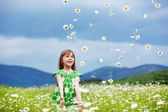 Child at camomile field — Stock Photo