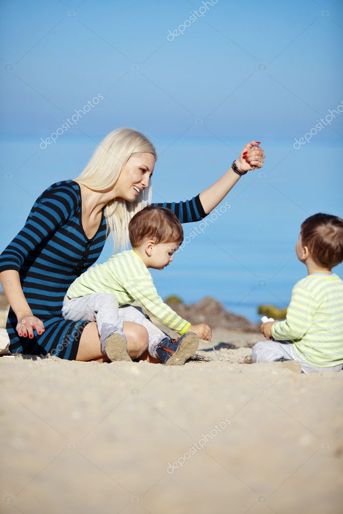 Young mother with her infant kids resting at the beach — Stock Photo #6434061