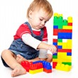 Stock Photo: Funny boy is playing with lego