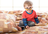 A boy in funny glasses on the bed — Stock Photo